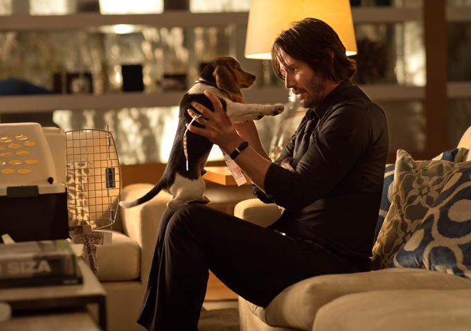 Keanu Reeves as John Wick holding up a dog